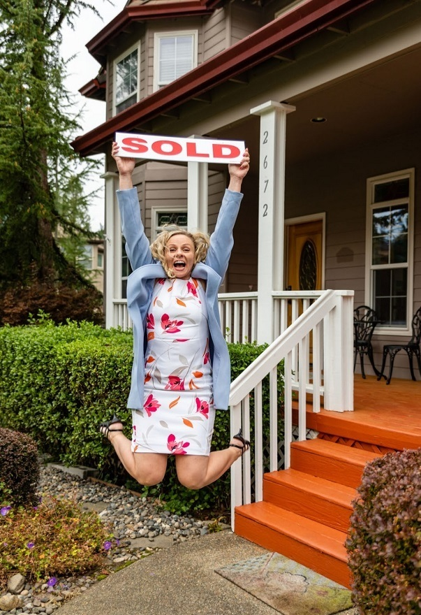 Korrie jumping with a sold sign